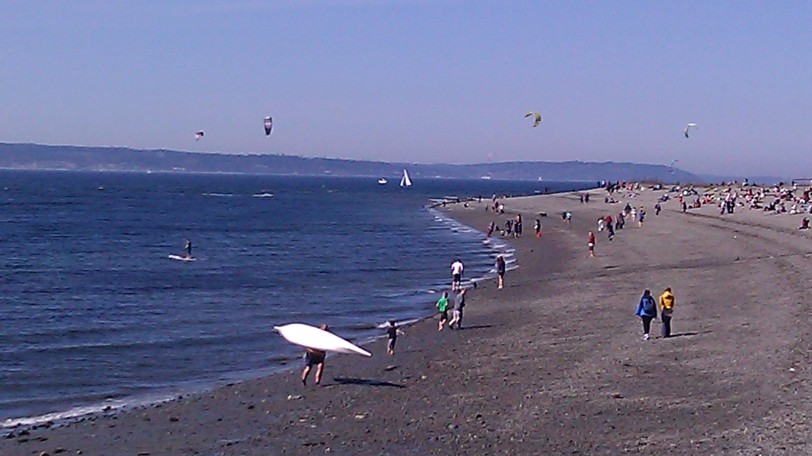 Kiteboarders, boaters and bathers enjoying the beach at Golden Gardens.